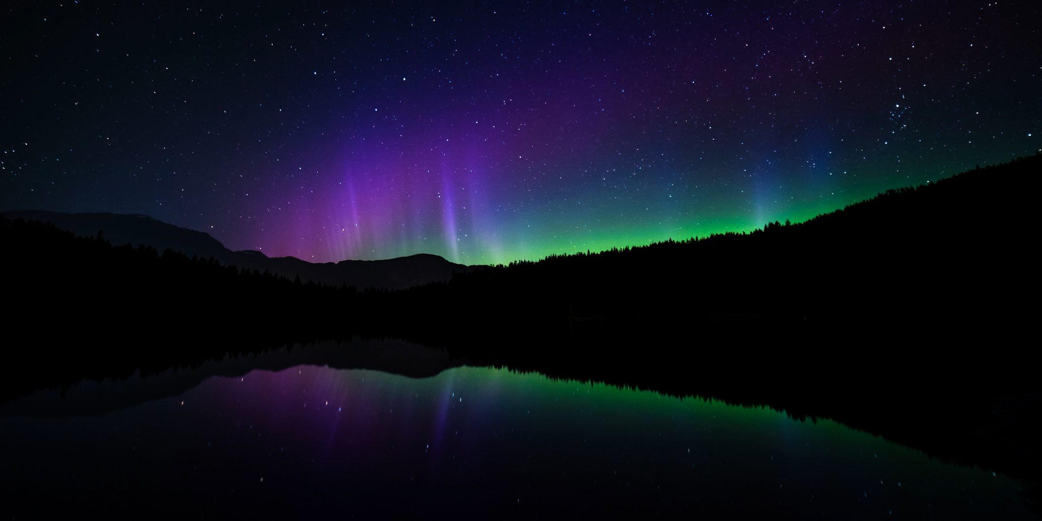 Northern Lights above a calm lake at night