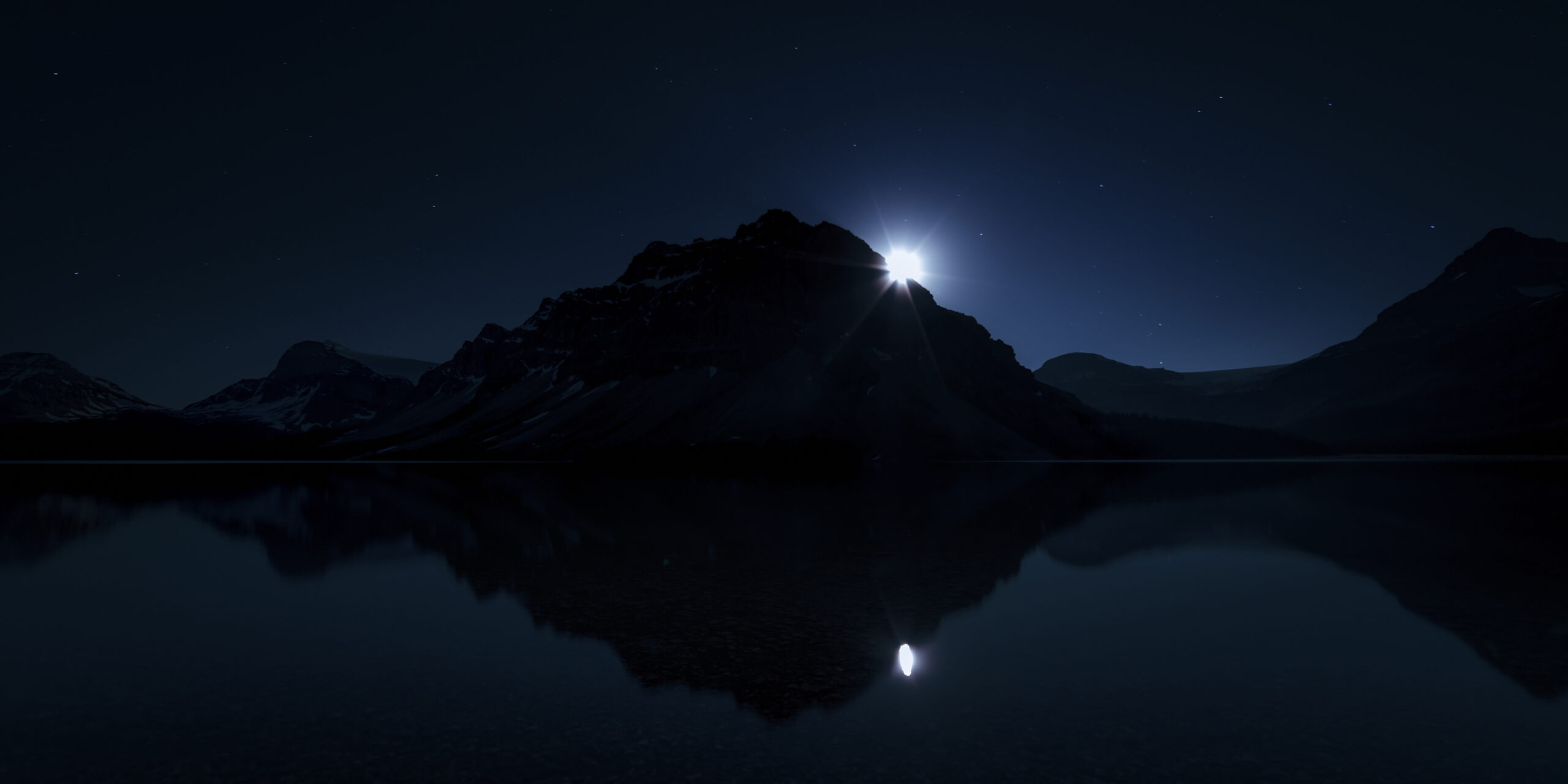Full Moon rises at glacier lake behind the silhouette mountains