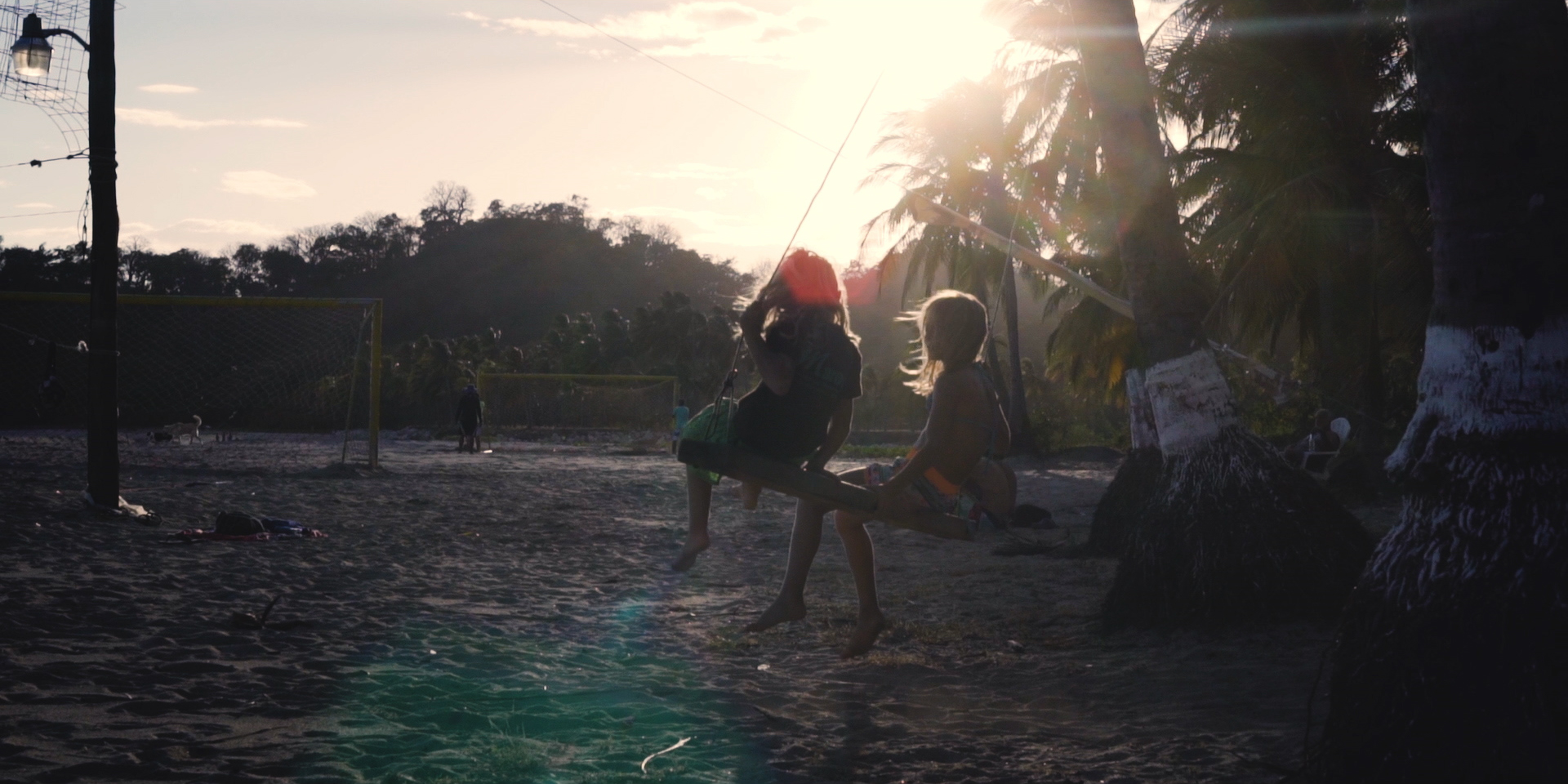 two girls swinging on beach during sunset